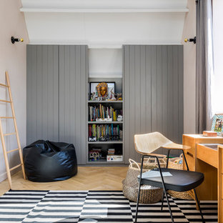 Inspiration for an industrial kids' study space in London with pink walls and light hardwood flooring.