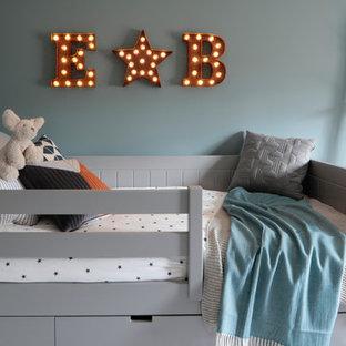 Cette photo montre une petite chambre d'enfant de 4 à 10 ans scandinave avec un mur bleu.