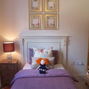 Immagine di una piccola cameretta per bambini da 1 a 3 anni tradizionale con pareti beige e moquette