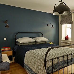 This is an example of a medium sized contemporary teen's room for boys in London with blue walls, light hardwood flooring and beige floors.