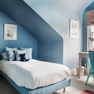 Photo of a contemporary kids' bedroom for boys in London with blue walls, carpet, beige floors and a vaulted ceiling.