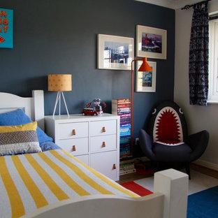 Ispirazione per una piccola cameretta per bambini da 4 a 10 anni eclettica con pareti blu, pavimento in laminato e pavimento marrone