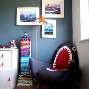 Inredning av ett eklektiskt litet pojkrum kombinerat med sovrum och för 4-10-åringar, med blå väggar, laminatgolv och brunt golv