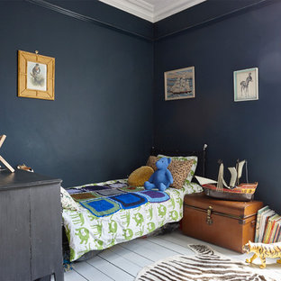 Photo of a large victorian kids' bedroom for kids 4-10 years old and boys in London with blue walls and painted wood floors.