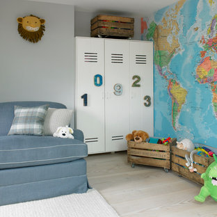 This is an example of a medium sized classic toddler's room for boys in London with grey walls, light hardwood flooring and beige floors.