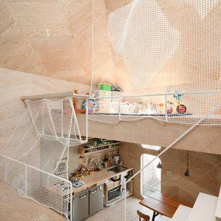 Esempio di una piccola cameretta per bambini da 4 a 10 anni industriale con pareti beige, pavimento in compensato e pavimento beige