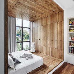 Ejemplo de dormitorio infantil minimalista con paredes marrones, suelo de madera en tonos medios y suelo marrón