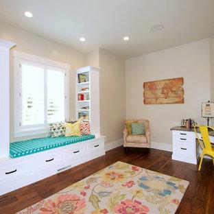 Immagine di una cameretta per bambini american style di medie dimensioni con pareti beige e pavimento in legno massello medio