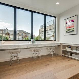 Modern inredning av ett barnrum kombinerat med skrivbord, med vita väggar och ljust trägolv
