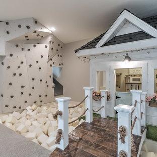 Bild på ett lantligt barnrum kombinerat med lekrum, med grå väggar, heltäckningsmatta och grått golv