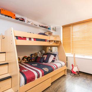 Ispirazione per una cameretta per bambini da 4 a 10 anni minimal di medie dimensioni con pareti bianche e pavimento in legno massello medio