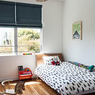 Imagen de dormitorio infantil de 4 a 10 años, moderno, pequeño, con paredes blancas, suelo de madera en tonos medios y suelo marrón