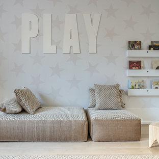 Playroom - scandinavian gender-neutral light wood floor playroom idea in New York with multicolored walls