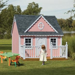 Immagine di una piccola cameretta per bambini da 4 a 10 anni vittoriana con pareti rosa, pavimento in compensato e pavimento marrone