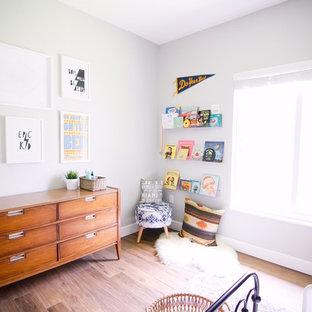Cette image montre une chambre d'enfant de 1 à 3 ans vintage de taille moyenne avec un mur gris et un sol en bois foncé.