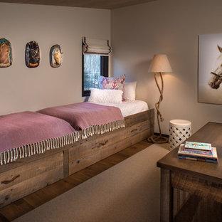 Modelo de dormitorio infantil de 4 a 10 años, de estilo de casa de campo, con paredes beige, suelo de madera oscura y suelo marrón