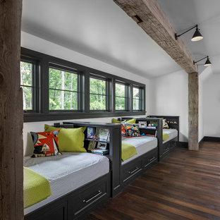 Foto på ett stort lantligt pojkrum kombinerat med sovrum och för 4-10-åringar, med vita väggar, mörkt trägolv och brunt golv