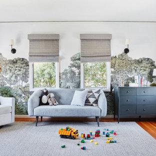 Esempio di una cameretta per bambini mediterranea con pareti multicolore, pavimento in legno massello medio, pavimento marrone e carta da parati