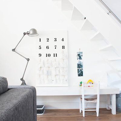 Eclectic gender-neutral light wood floor kids' study room photo in Amsterdam with white walls
