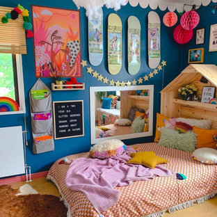 This is an example of an eclectic kids' room for girls in Melbourne with blue walls, medium hardwood floors and brown floor.