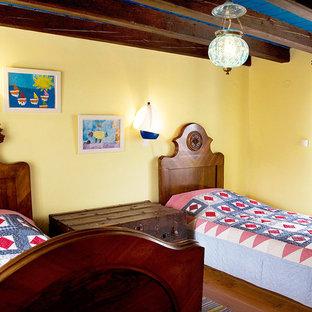 Immagine di una cameretta per bambini mediterranea con pareti gialle e pavimento in legno massello medio