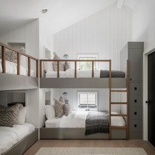 Пример оригинального дизайна: нейтральная детская в стиле кантри с спальным местом, белыми стенами, паркетным полом среднего тона, коричневым полом и стенами из вагонки