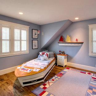 Immagine di una cameretta per bambini da 1 a 3 anni costiera di medie dimensioni con pavimento in legno massello medio e pareti viola