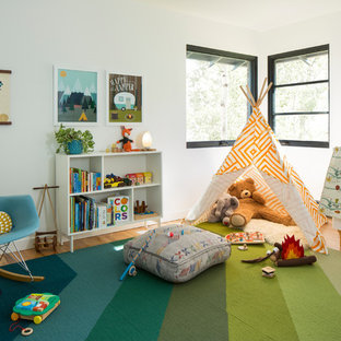 Example of a 1950s gender-neutral medium tone wood floor kids' room design in Denver with white walls