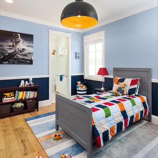 Foto di una cameretta per bambini da 1 a 3 anni tradizionale con pareti blu, parquet chiaro e pavimento beige