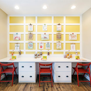 This is an example of a medium sized classic gender neutral children's room in Salt Lake City with yellow walls and medium hardwood flooring.