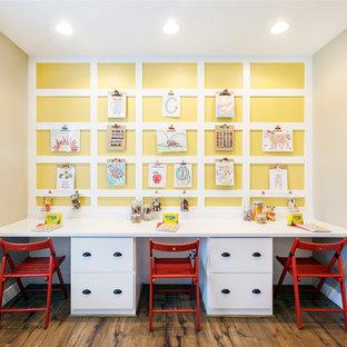 Bild på ett mellanstort vintage könsneutralt barnrum för 4-10-åringar och kombinerat med skrivbord, med gula väggar och mellanmörkt trägolv