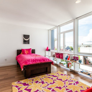 Photo of a contemporary kids' bedroom for kids 4-10 years old and girls in Seattle with white walls and medium hardwood floors.