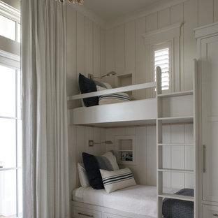 Example of a coastal gender-neutral dark wood floor and brown floor kids' bedroom design in Miami with white walls