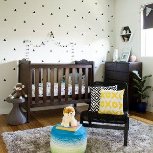Foto på ett mellanstort funkis barnrum kombinerat med sovrum, med beige väggar och ljust trägolv
