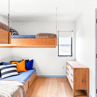 Inspiration for a mid-sized contemporary boy medium tone wood floor and brown floor kids' room remodel in New York with white walls