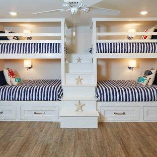 Ispirazione per una grande cameretta per bambini stile marino con pavimento in legno massello medio e pavimento marrone