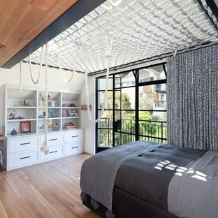 Photo of a traditional kids' room for boys in San Francisco with white walls, medium hardwood flooring and brown floors.