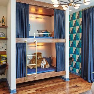 Foto på ett stort funkis pojkrum kombinerat med sovrum och för 4-10-åringar, med vita väggar och mellanmörkt trägolv
