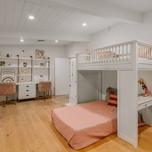 Photo of a large midcentury kids' bedroom for kids 4-10 years old and girls in Los Angeles with white walls, light hardwood floors and beige floor.
