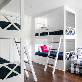 Esempio di una cameretta per bambini da 4 a 10 anni stile marino di medie dimensioni con pareti bianche, pavimento in legno massello medio, pavimento marrone e pareti in perlinato