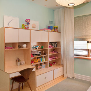 Trendy gender-neutral light wood floor kids' room photo in New York with blue walls