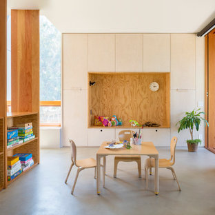 Example of a trendy concrete floor and gray floor kids' room design in Los Angeles with white walls