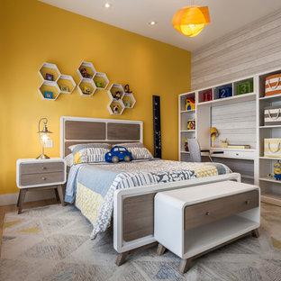 Inspiration för ett mellanstort funkis pojkrum kombinerat med sovrum och för 4-10-åringar, med plywoodgolv och gula väggar