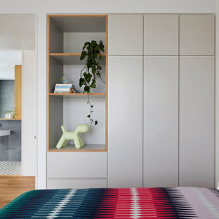 This is an example of a contemporary gender-neutral kids' room in Melbourne with grey walls and light hardwood floors.