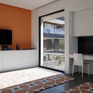 Immagine di una grande cameretta neutra da 4 a 10 anni american style con pareti arancioni, pavimento in cemento e pavimento grigio