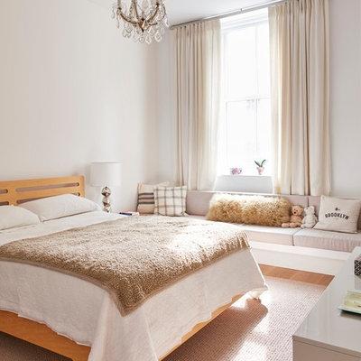 Example of a trendy girl brown floor and medium tone wood floor kids' bedroom design in New York with white walls