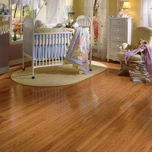 Ispirazione per una grande cameretta per bambini da 1 a 3 anni chic con pareti gialle e pavimento in legno massello medio