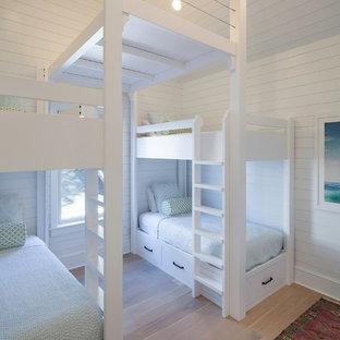 Foto på ett maritimt barnrum kombinerat med sovrum, med ljust trägolv och vita väggar