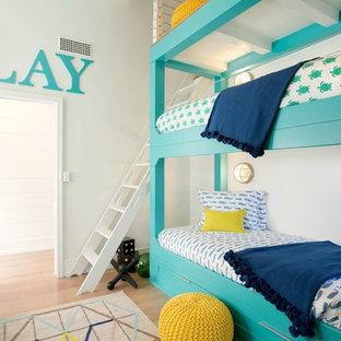 Idéer för att renovera ett mellanstort maritimt könsneutralt barnrum kombinerat med sovrum och för 4-10-åringar, med vita väggar och mellanmörkt trägolv