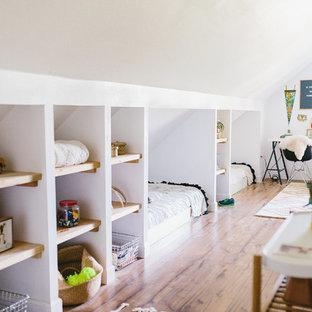 Foto di una grande cameretta da letto country con pareti bianche, pavimento in laminato e pavimento marrone